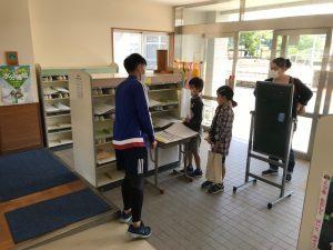 靴箱ポスト前で学習課題の受け渡しをしている先生と児童